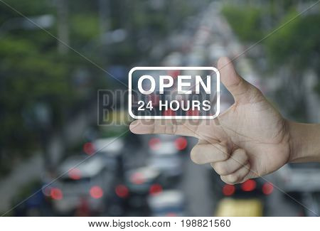 Open 24 hours icon on finger over blur of rush hour with cars and road e-business concept