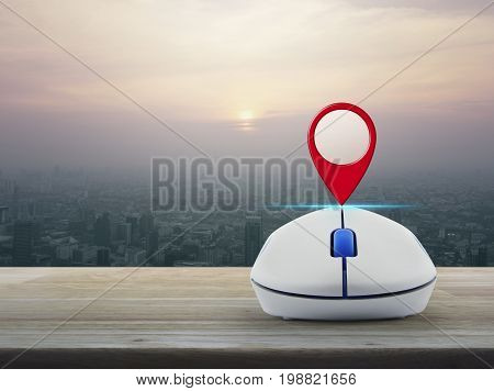 Map pin location button with wireless computer mouse on wooden table over modern city tower at sunset vintage style Map pointer navigation concept