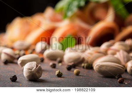 A close-up picture of light brown pistachios with black pepper, basil leaf and cut ham on a black blurred stone table background. Nutritious bar appetizers. Nuts full of vitamins.