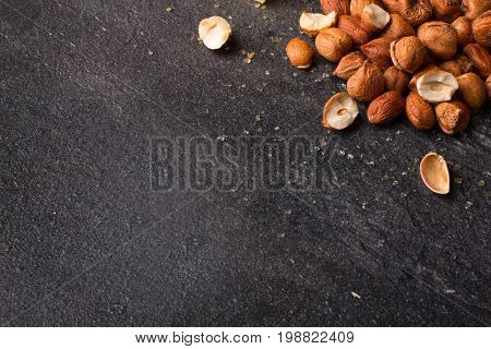 A view from above on salty appetizer for beer on a saturated black stone background. Small heap of nutritious roasted crispy hazelnuts. Peeled brown nuts. Copy space.