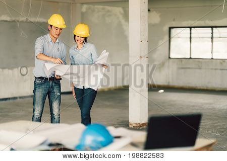 Young Asian engineers couple working on building blueprint at construction site. Civil engineering industrial or home renovation concept. With copy space
