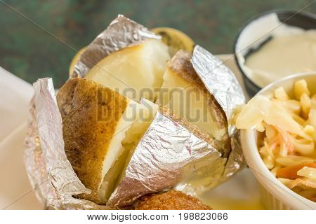Fresh Hot Baked Potato Wrapped In Aluminum Foil And Cut Open Into Quarters, Plain