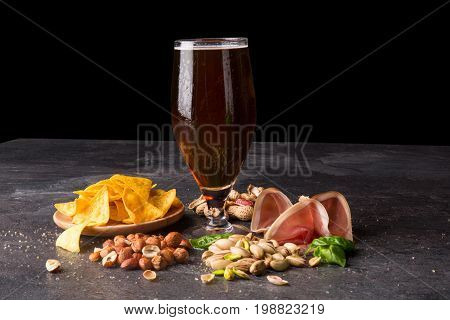 Beautiful nutritious traditional snacks next to a big pint of dark beer on a black background. Nacho chips in a plate and sliced prosciutto. Peeled peanuts and appetizing pistachios. Copy space.