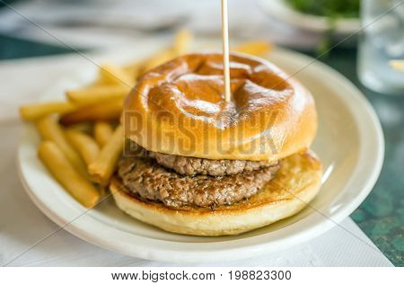 Juicy Double Hamburger With Toasted Bun Held Together With Long Pick, No Condiments