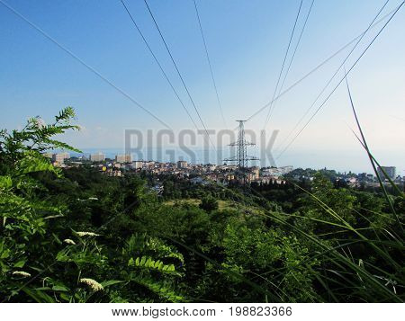 View from the mountain to the trees wires power line support and village