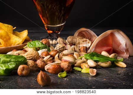 A beautiful set of nutritious traditional snacks next to a big pint of dark ale on a black table background. Nacho chips in a plate and peanuts. Sliced bacon and appetizing pistachios. Copy space.