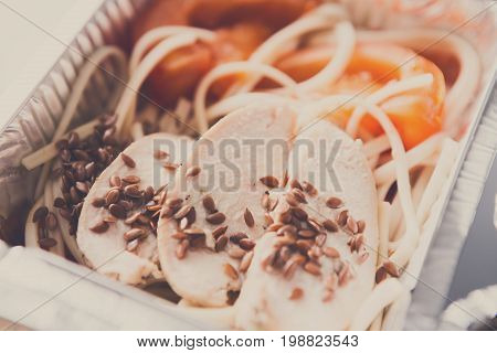 Healthy lunch in foil container. Healthy food take away and delivery. Durum wheat pasta, steamed turkey, fresh vegetables and flax seeds in box on white background, closeup, vintage filter