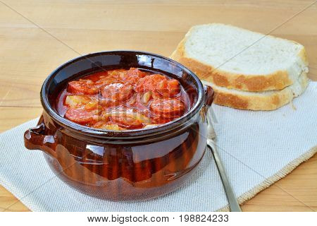 Vegetable stew with sliced sausage lecho in ceramic pot with bread