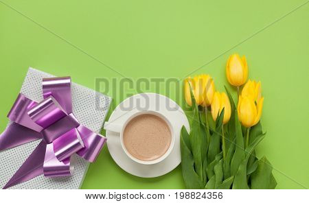 From above shot of yellow tulips on green table with giftbox and cup of coffee.