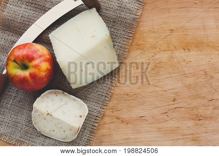Cheese background. Gouda pesto cheese, apple and cheese knife on sackcloth on wooden table, still life, copy spase
