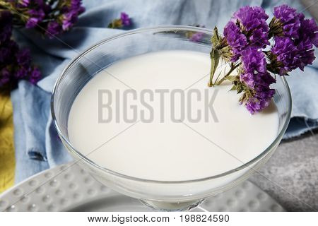A close-up picture of a white, organic and vegetarian non-alcoholic milkshake in a glass on a bright blue background. A margarita glass with a refreshing cocktail and purple flowers.