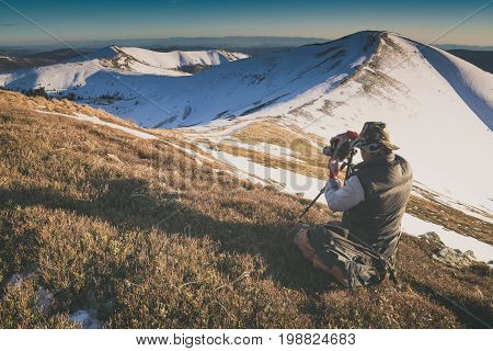 Photographer with a camera taking photos of beautiful winter mountain valley in a morning light. Instagram stylization.