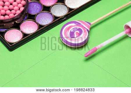 Pink and purple make up products: lip gloss, eyeshadow, blush with lollipop. Harmonious color combination in makeup. Copy space