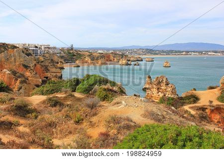 Beautiful landscape overlooking Atlantic ocean coast line in   Lagos, south Portugal. Summer nature panoramic scene: hills, water, beach and clear blue sky background. Photo of long distance outdoor sunny day view