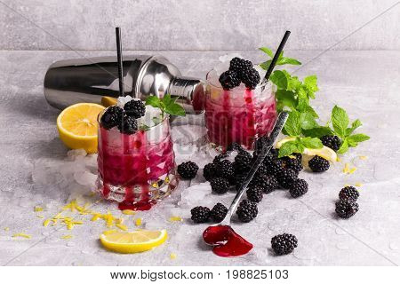 Couple of fancy glasses full of cold, icy beverage with spearmint, lemon pieces, juicy blackberries and black straws on a frozen gray table background. Refreshing cocktails with fruits and berries.