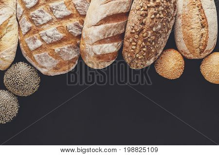 Bakery background, bread assortment isolated on black. Top view with copy space