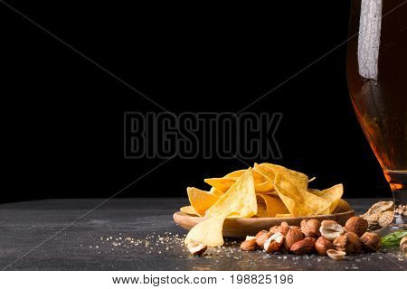An alcoholic drink and tasty snacks on a black background. A plate of yellow crispy nachos and pile of nutritious nuts next to a glass of fresh golden beer. Copy space.