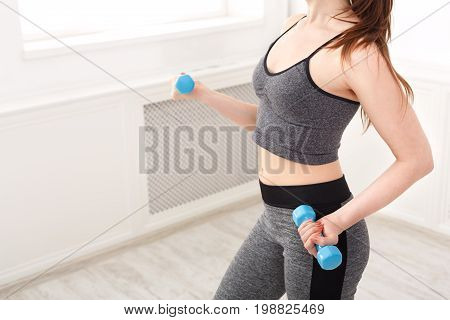 Fitness model woman with dumbbells, torso crop. Young girl in fitwear at white background