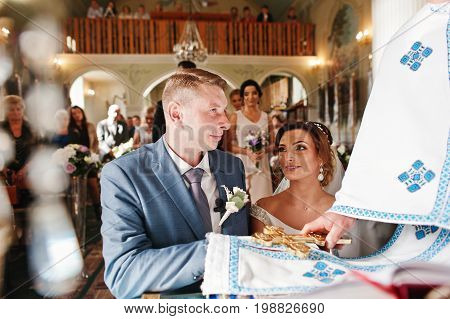 Beautiful Wedding Couple Making Vows During Wedding Ceremony In The Church.