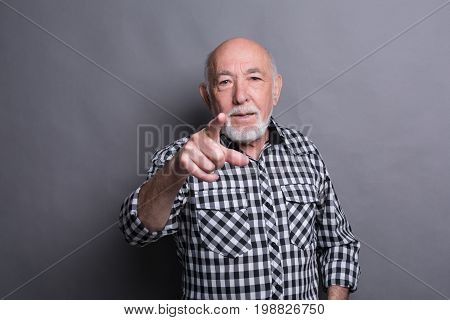 You are the next. Mature man in casual wear point at camera while standing against grey background
