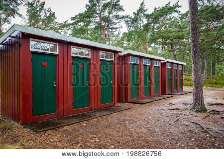 Many red and green wooden outhouse toilets in a row in a forest park.