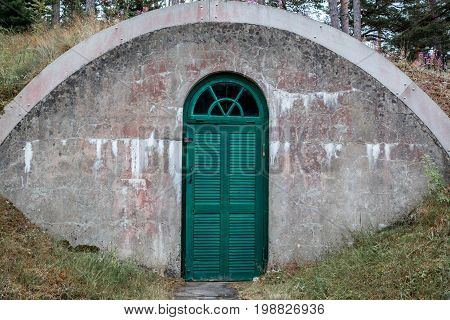 A weathered arched outdoor concrete underground cellar with green wooden door for food storage.