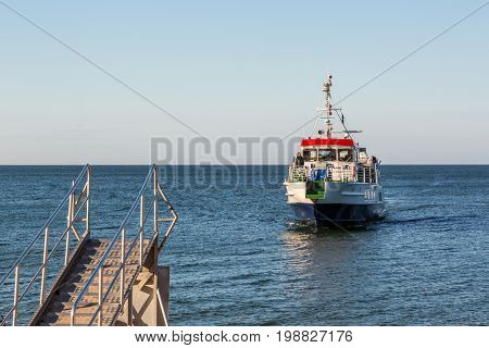 Boat approaching shore to pick up people. Gotska sandon Sweden - August 2 2017: View from the shore of a passenger boat at the Baltic sea approaching a gangway at the island Gotska sandon to pick up tourists. Crew can be seen standing on the deck.