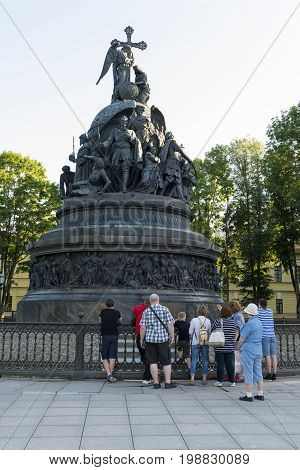 group of tourists several people men and women stand near the monument to the Millennium of Russia Novgorod Kremlin