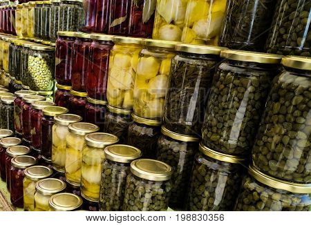 Rows of colorful glass canning jars filled with food from grandmother's kitchen.