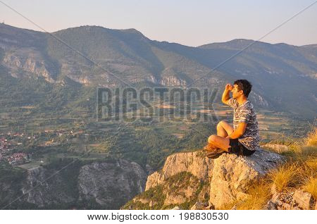 Young man sits on a cliff edge on the top of mountain with gorgeous view. Dangerous Place. Adrenaline.
