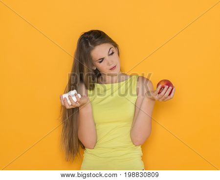 Difficult choice between sweets and healthy food, diet dieting concept. Young pretty woman in yellow dress make her selection.