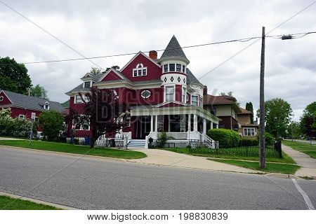CADILLAC, MICHIGAN / UNITED STATES - MAY 31, 2017: An elegant red Victorian mansion, with a wraparound porch and a turret, in the Courthouse Hill Historic District of Cadillac, Michigan.