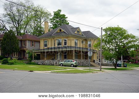 CADILLAC, MICHIGAN / UNITED STATES - MAY 31, 2017: A charming yellow brick Victorian mansion, with a wraparound porch and elegant stonework, in the Courthouse Hill Historic District of Cadillac, Michigan.