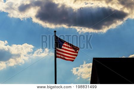 Flag of the USA against the sky with clouds The American Flag Flying Against A Blue Sky With White Clouds On A Windy Day
