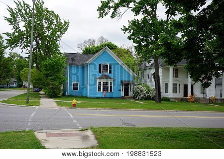 CADILLAC, MICHIGAN / UNITED STATES -  MAY 31, 2017: A lovely blue home with a bay window flies the American flag in Cadillac's Courthouse Hill Historic District.