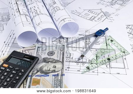A blueprint of an architect with money calculator. symbolic photo for financing and planning of a new house. Blueprints rolls and a drawing instruments on the worktable