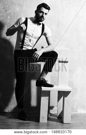 bearded man long beard brutal caucasian hipster with moustache in white shirt and suspenders with bow-tie posing next to wooden chair with serious face on studio wall background