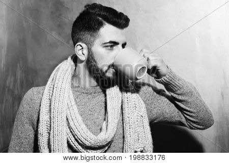 bearded man long beard brutal caucasian hipster with moustache dressed in sweater and scarf drinking tea or coffee from grey cup with serious face on brown studio wall background