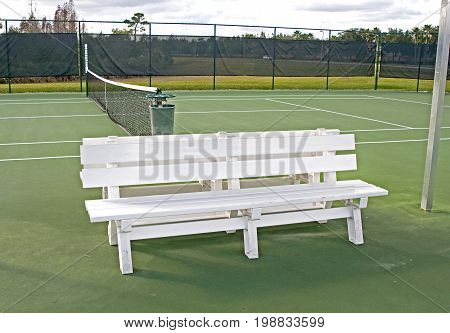 White bench on the side of a tennis court, on an overcast afternoon in Tampa, Florida, USA