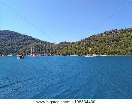 Sea, sky, boats, summer, sunny day, yachts near picturesque hilly coast. Blue and gree pure natural colors. The concept of  water trips