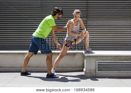 Young Couple Stretching In The Urban Environment