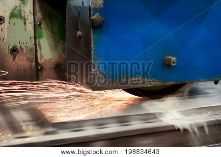 Work of an industrial surface grinding machine. Grinding of a flat metal part. Sparks fly out from under the grinding wheel. Grinding with a coolant.