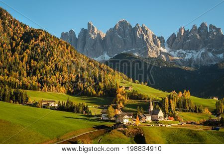 St. Magdalena or Santa Maddalena with its characteristic church in front of the Geisler or Odle Dolomites mountain peaks in the Val di Funes valley (Villnoesstal) in Italy in autumn.