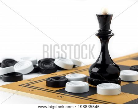 The chess queen and checkers placed on the chessboard. White background