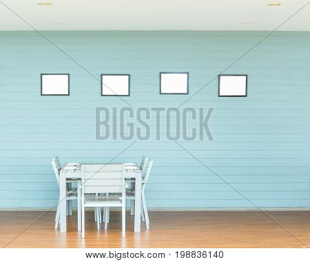 Wooden Dining room table and chair and blank frames for your text image or logo or even family pictures.