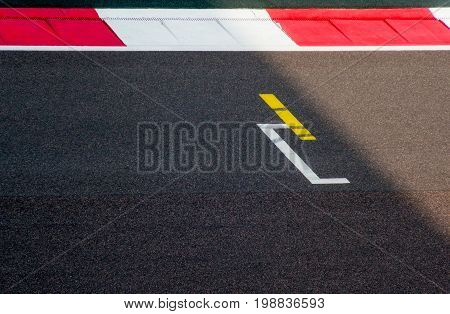 Starting line and red white boundry of a racing track. Starting point of an event or project. Plenty of space for copy