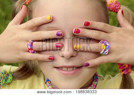 Children's multicolored manicure with stripes on a light girl with rubber bands on a summer day.