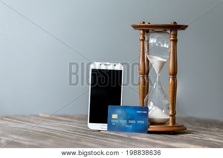 Credit card and mobile smart phone, Online shopping. Concept of time management. Sand clock