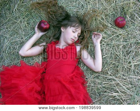 little girl in red dress sleeping on the haystack in summer day