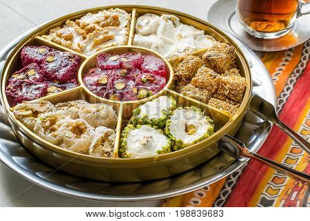 Eastern sweets. Assorted traditional Turkish delight (Rahat lokum). Turkish delight with different nuts and coconut shavings tea in glass (armud) and tongs for sweets